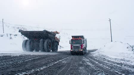 mamut : Siberia, Russia - January 24, 2015: Mining dump truck driving on snowy road from coal cut in Russia. Machinery for heavy industry carrying fossil. Car with huge wheel. Work for dirty environment