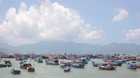 Ships and boats for fishing near the lakeside in morning. Scenery with port or dock and coast for catching fish. Mountains in the fog on island on horizon. National ethnic culture with ocean or sea