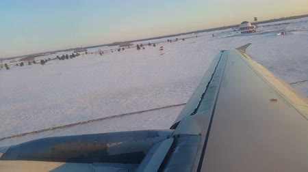 уменьшающийся : Plane picks up speed on landing strip. Take off on background of snowy field. View from cabin or cockpit to window or porthole. Wing of plane shakes, anxious passengers. Fast start and rise to air Стоковые видеозаписи