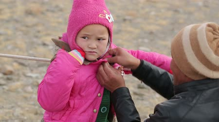 tiller : Bayan-Ulgiy, Mongolia - November 5, 2014: Festival golden eagle hunting. Buttoned jacket daughter. Mother dress daughter Stock Footage
