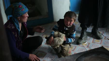 heir : Bayan-Ulgiy, Mongolia - November 6, 2014: Little nomad with his mother. Mistress puts a cap on his son in the home of shepherds Stock Footage