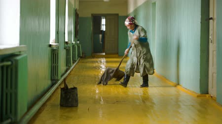 sprzataczka : Deluun, Mongolia - November 9, 2015: Cleaner washes the floor of the school during lessons. Pupils sitting in the classroom, in the hallway silence. In the Mongolian settlement. Documentary footage