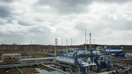 Modern facility with pipes or powerful process area at the oil depot or tank farm. Gas technical complex for refining rock-oil and supply. Timelapse in cloudy autumn. Sky with clouds. Day landscape