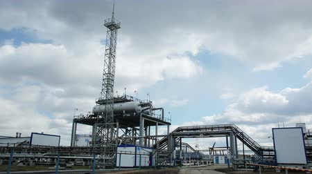 Modern facility with pipes or powerful process area at the oil depot or tank farm. Technical complex for refining rock-oil and supply. Timelapse outdoors in cloudy autumn. Blue sky with clouds. Nobody Stock mozgókép