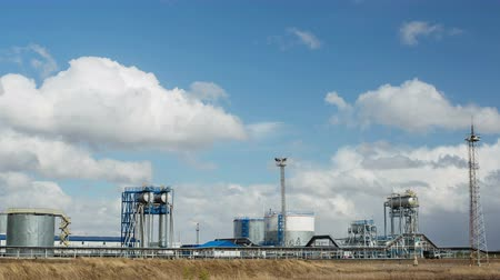 Modern facility with pipes and tower or powerful process area at the oil depot or tank farm. Technical complex for refining and supply. Timelapse outside in cloudy autumn. Blue sky with clouds. Day