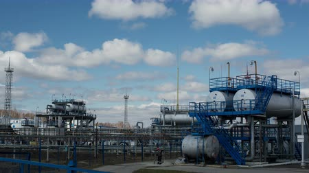 Modern facility with pipes or powerful process area at the oil depot or tank farm. Technical complex for refining rock-oil and supply. Timelapse of work outdoors in cloudy autumn. Blue sky with clouds