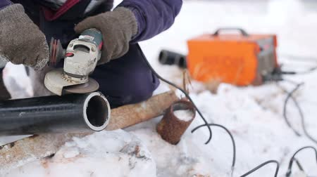 Man in protective clothing repairing a pipe in the winter, prepares pipe for welding. Outside the snow and cold. Male severe job. Hard work with angle grinder. Close up of arms outdoors. Manual labor