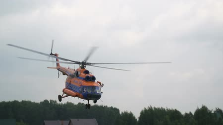 mi : Novosibirsk Russia - July 31 2016: Russian military helicopter in air. Fly in gray cloudy sky and perform maneuver slowmo. Motion on airbase or airdrome. Accuracy of action and moving slomo Stock Footage