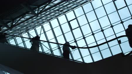Movement of people on the moving stairway inside the structure of financial company or public place with large glass windows. Metaphor of society economy. Blue color of sky and silhouettes of nation