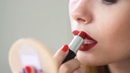 Girl apply lip stick looking in mirror holding hand. Beautician is making perfect look by professional cosmetics close up, admiring natural complexion and pure skin. Beauty treatment. Natural lighting Vídeos
