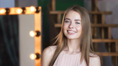 elegancia : Youth portrait of carefree 20s lady posing for camera with enjoyment. Happy trendy teen girl is looking at camera or away with smile. Harmonious image of innocence and freedom. Home dusky background Stock mozgókép