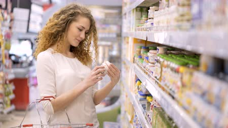 grocery : Cute 30s brunette model with long curly hair makes purchases in department store close up. Young mom selects puree, juices for child and puts baby food in basket holding hand. Consumer society concept Stock Footage