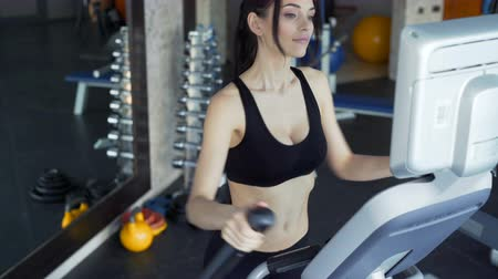 elliptical : Portrait of 20s with sports clothing train in gym club indoors interior. Build beauty and vitality. Brunette with slender physique closeup. Speed moving technology, track for walk or jog. Cute face