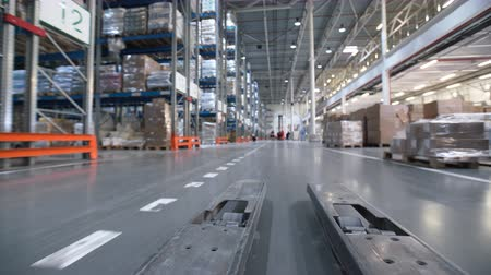 dağıtım : Vehicle trucks move at large rows between shelf with cardboard boxes, products, inventories and containers in professional stockroom interior. Workers are drive and do control of logistics job