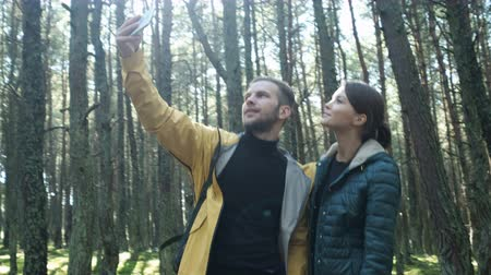 pic : Two person: girlfriend and boyfriend making a pic at beauty natural background with treeline in beauty sunrise. Male and female trendy caucasian hiker doing photosession together use the cellphone app Stock Footage