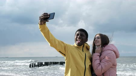 pic : Two multicultural persons of black guy and cute white lady make a photography at smartphone closeup. Positive funny concept of relations at autumn vacation, cellphone for take a pic with beachfront Stock Footage