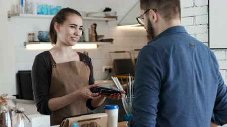 caixa : Adult female employee near cash desk of restaurant store with creative interior for breakfast or lunch. Nfc cellhone of male buyer with cashless wallet of e-money for pos card reader and checkout