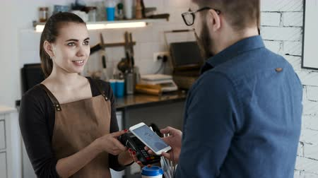 payment terminal : Attractive female employee near cash desk of restaurant store with creative interior for breakfast or lunch. Nfc cellhone of male buyer with cashless wallet of e-money for pos card reader and checkout