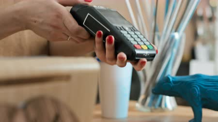 job transfer : Female employee near cash desk of restaurant store for breakfast or lunch. Plastic debit card of male buyer with cashless wallet of e-money for pos reader and checkout. Morning life of people slowmo Stock Footage
