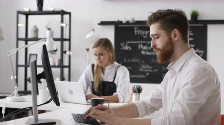Trendy beautiful 20s colleagues sitting at desktop monitor on table close up indoors. Busy male caucasian person in bright loft studio room for idea of financial job or internet start up. White collar Stock mozgókép