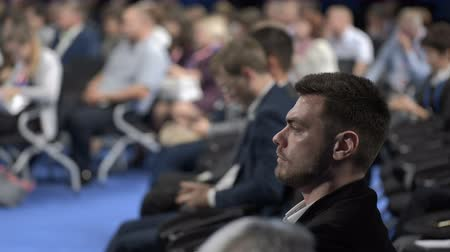 Crowded congress in marketing center indoors. Businesspeople looking economy information for leadership or cooperation strategy of young banking company. Adult listener or spectator sitting on chair