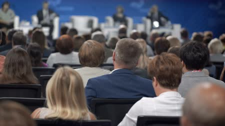 auditório : Listener at economic congress of corporation. Politicians view sale show on crowded row of chair seats. Education expert occupation for professional communication indoors. White collar in large room