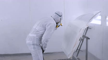 repaint : A professional car painter is painting the body work of a car in a paint box of a garage with an airbrush.