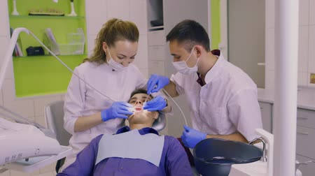 stomatologia : Dentist and his assistant examine a patient