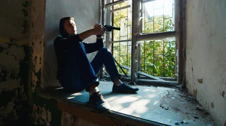 guerrilla : A man with a gun sitting on a window sill. Concept: despair, hope, crime Stock Footage