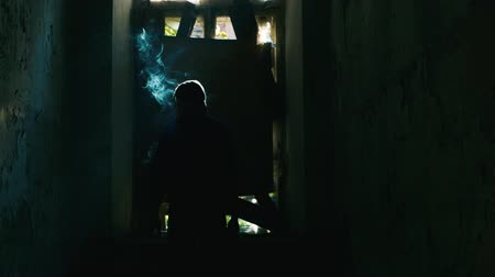 опасность : Silhouette of male smokers in an abandoned house. Concept: crime, danger
