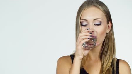 içme : Attractive blonde woman drinks water on a white background