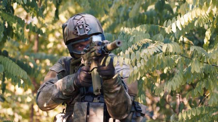 ohař : A man in military camouflage hiding in the foliage, takes aim