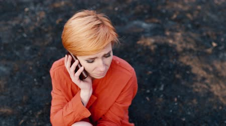 clientes : Very sad red-haired woman sitting on burnt grass, holding a phone to the ear. Concept: need help, sadness, loneliness