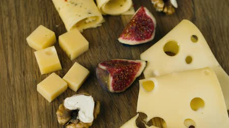 fresh cheeses : A set of different cheeses with figs, turns to the camera Stock Footage