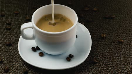 coffee brewing : Pouring cream into a cup of coffee Stock Footage