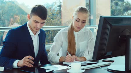 проект : A man and an attractive woman working in the office at the table: check data in the documents
