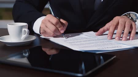 advokát : Mans hand in a business suit signs documents