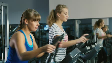 elliptical : At a training session. Two attractive women are trained in the gym Stock Footage