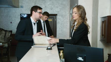отель : Check into a hotel. Businessmen filled with documents at the reception of the hotel