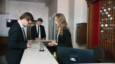 temsilci : Check into a hotel. Businessmen filled with documents at the reception of the hotel