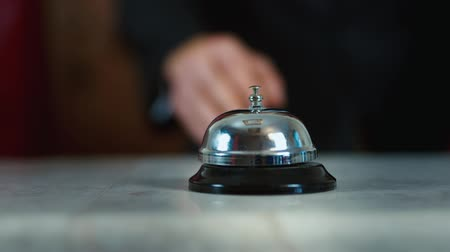 отель : Hand strikes the bell on hotel reception