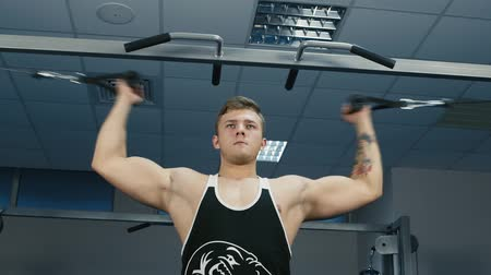 güçlü : The man trains the biceps muscle on the block device