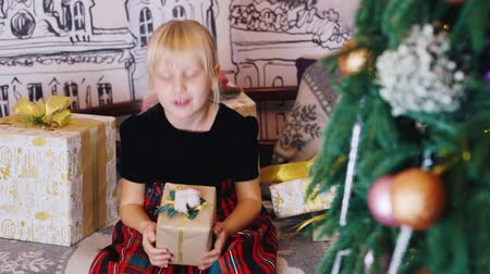 капелька : Girl looking at Christmas presents near the Christmas tree