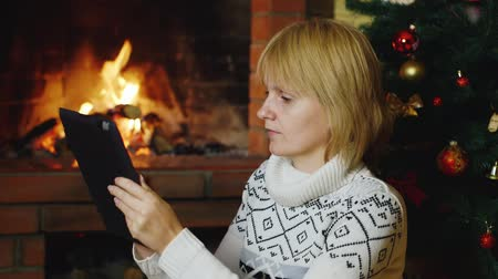 cozy : Woman works with a tablet near the fireplace and Christmas tree