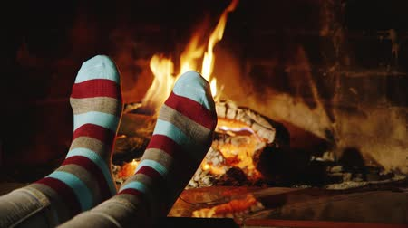 ayaklar : The girl warms his feet by the fireplace. Concept: warmth and comfort of home