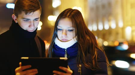 podróżnik : A young couple standing on the background of the city at night and looking at the screen of the tablet Wideo