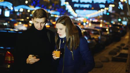 ночная жизнь : Young man and woman talking in the night city Стоковые видеозаписи