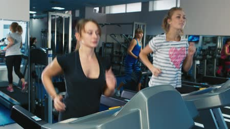 fogyás : Two women running on the treadmill in the gym