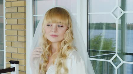 blond vlasy : Young attractive bride looks in the mirror. She has blonde hair and blue eyes