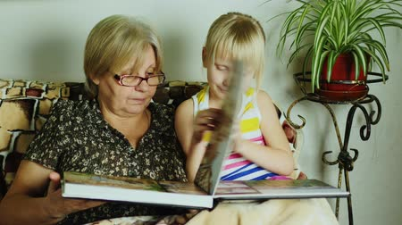 lineage : A girl with her grandmother looking photo album